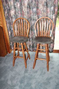 A pair of wooden upholstered self-righting swivel bar stools