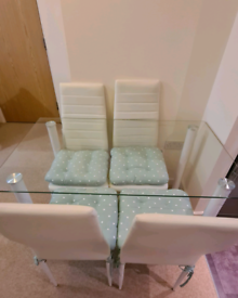 (Negociable) Glass dining table with 4 chairs and cushions included.