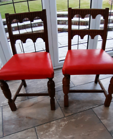 Pair of dark oak carved dining chairs with turned legs leather seat