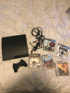 Ps3 console and games with controllers and cords.