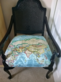 Rattan backed chair with a padded seat covered in a map design fabric