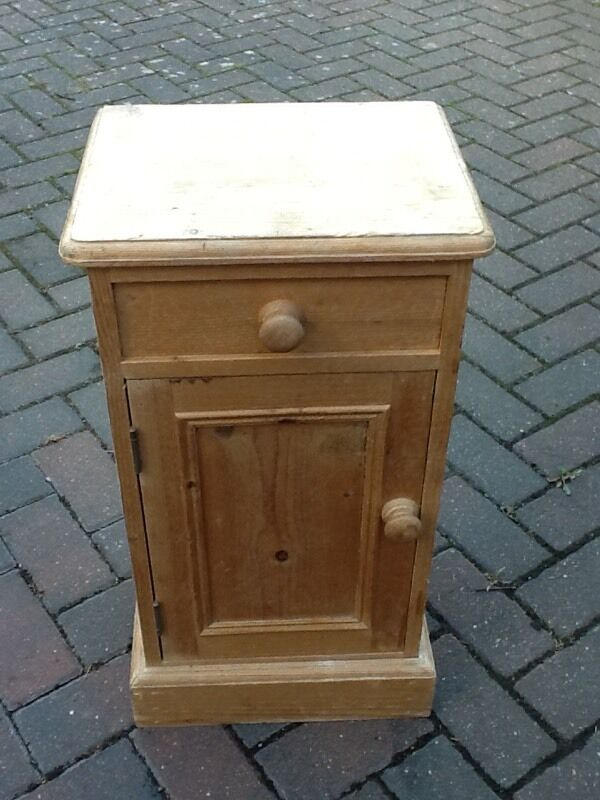 A SMALL BARE PINE BEDSIDE TABLE IN NEED OF REFURBISHMENT