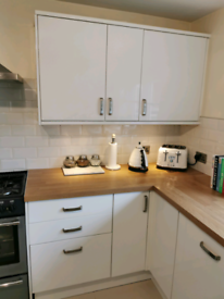 Howdens high gloss white slab kitchen doors with silver handles