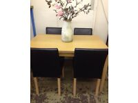 Modern light wood table and four faux leather brown chairs