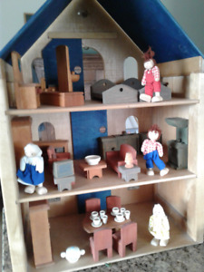 Wooden dollhouse with lots of plan toys furniture.