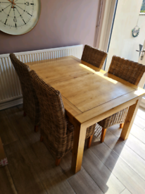 Solid oak extending table and wicker chairs