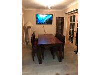 Solid wood dining table with 6 chairs and cushions.