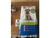 puppy training pads and a can of puppy food