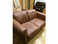 Tan soft leather two seater sofa and footstool