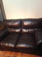 Black leather love seat couch.
