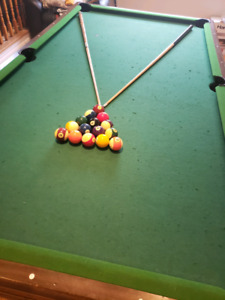 Pool table in good condition with cues and stand