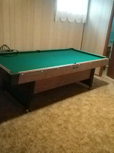 Pool table with sticks and pool balls plus tennis board