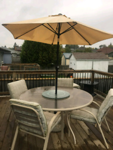 Patio table, chairs, footstools, and umbrella
