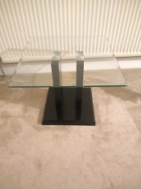 clear glass coffee table with a black base.