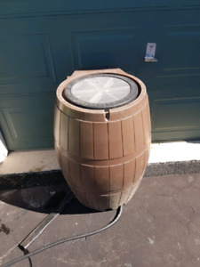 Brown plastic water barrel.