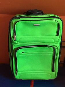 Bright green soft sided wheeled suitcase