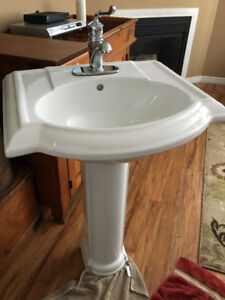 White pedestal sink complete with Moen single lever tap