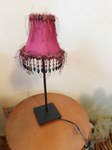 Retro look metal desk lamp with frilly cranberry shade working