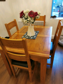 Solid oak dining room table with 4 chairs.