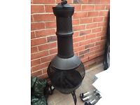 Black metal garden Chiminea with cover.