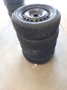 SET OF 4 SNOW TIRES ON STEEL RIMS IN ALMOST BRAND NEW CONDITION