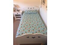 Single white bed with storage drawer and bedside table