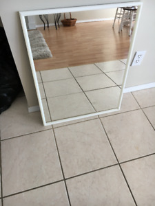 Large white mirror incased in a white plastic frame