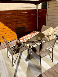 Patio table, four chairs, and umbrella