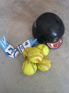 Five slowpitch softballs and batting helmet