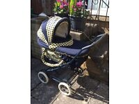 Pram with carrycot and adjustable seat.