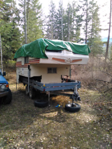 Truck camper and tandem axel trailer.