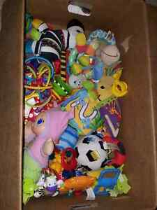 Box of GUC baby toys and nursing cushion