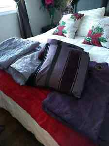 Purple bed spread, pillow cases, throw pillows, curtains.