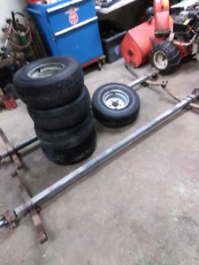 Trailer axles with new tires.
