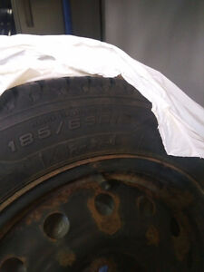 185x65R15 winter tires with rim on it.