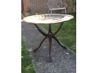Old brass table with carved wooden legs