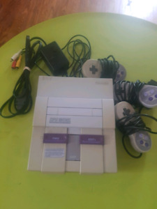 SNES console with cords and 3 controllers