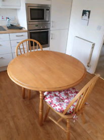 A round dropleaf dining/kitchen table with 2 chairs. 107cms diameter
