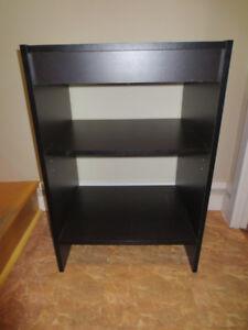 Petite bibliothèque noire, peut servir de table de chevet.
