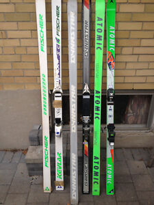 downhill skiis of various kinds and makes