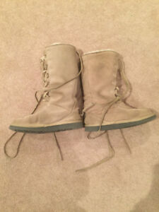 Beige and a black pair ugg laced high boots