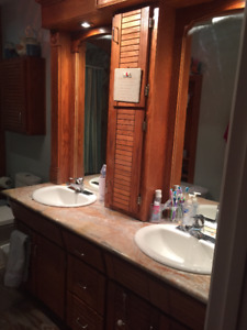 Bathroom vanity in cherry color oak with marble top and sinks.