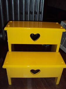 Yellow wooden step stool stands 15 inches high.