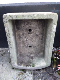 A old concrete sink with two plug holes what was used for a pond in a