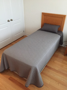 Single bed with box spring and wood headboard.