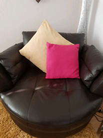 Large brown leather swizzle love chair.