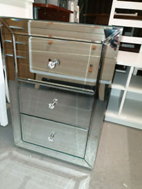 A new stylish large mirrored three drawer bedside table.