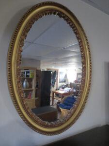 Joli miroir ovale couleur or.