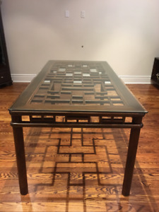 Wood dining table with Asian-inspired latticework and glass top