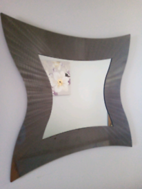 Wall mirror in a wavy shape in silver colour